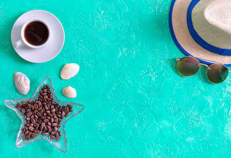 Cup of coffee, roasted coffee beans, hat and sunglasses. Top view, flat lay. Sea style. Vacation background with copy space. Stock Photo