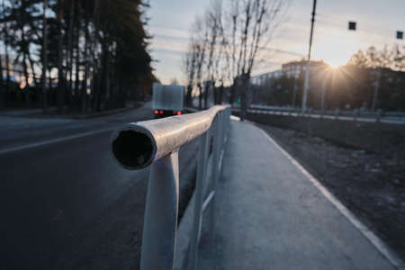 Street fence at sunrise, city stream of cars stands in traffic.