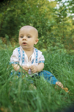 ukrainian ethnicity: beautiful baby in the embroidery on the green grass