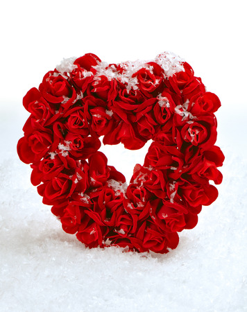 easter candle is burning: Red stone heart in artificial snow Stock Photo