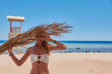 Young girl enjoying sun, relaxing on sea beach and holding palm branch.