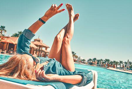 Pretty woman lye on a lounger near a swimming pool. Reklamní fotografie