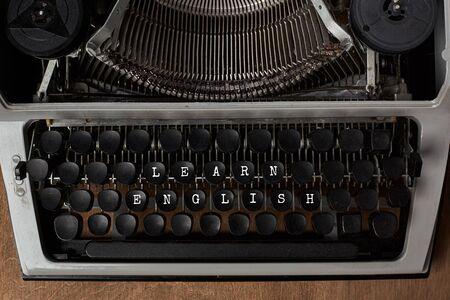 """Antigua máquina de escribir mecánica vintage con el texto """"Aprender inglés"""" en las teclas. Concepto de aprendizaje del idioma inglés."""