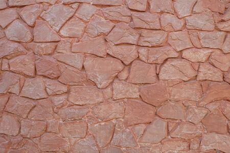 Uneven red sandstone tiles wall texture background.