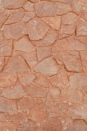 Uneven red sandstone tiles wall texture background vertical
