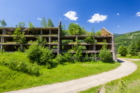 Unfinished abandoned building overgrown with trees