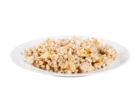 kasha: Barley porridge with onions on a white plate