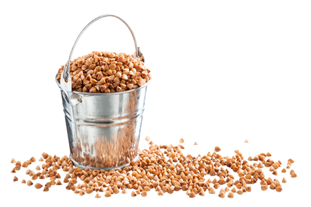 Buckwheat groats in a bucket on a white background