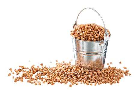 Buckwheat groats in a bucket on a white background