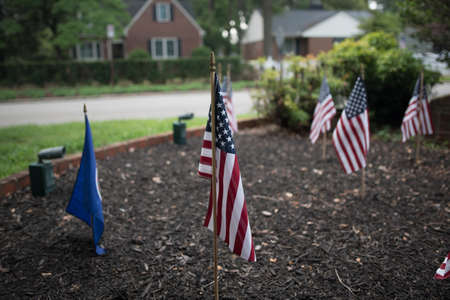 Mini American flag stuck in the ground during Fourth of July. Reklamní fotografie