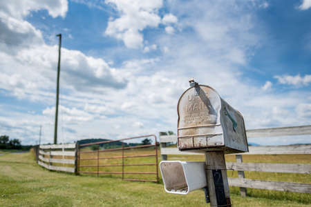 Close up shot a mailbox with open field and sky behind it.
