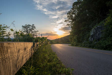 Bend in the road on the Blue Ridge Parkway with bright early morning sky.