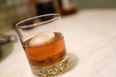 Whiskey on the rocks in glass sitting on kitchen counter.