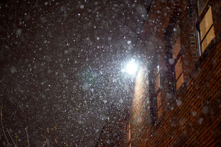 Snow falling near an apartment complex.