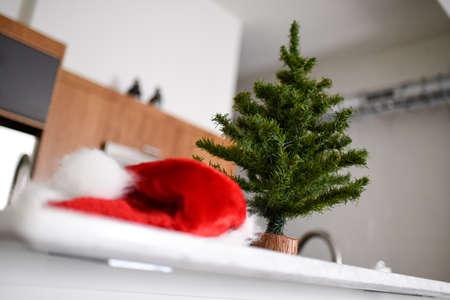 Mini Christmas tree on kitchen counter with santa hat.