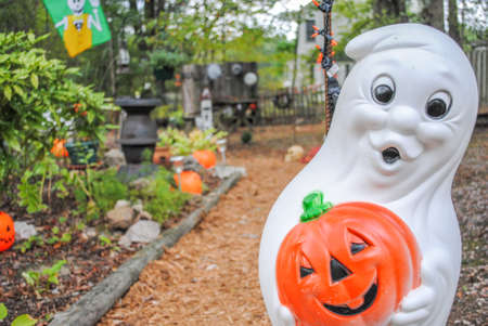 Friendly ghost halloween decoration with fall leaves on the ground.