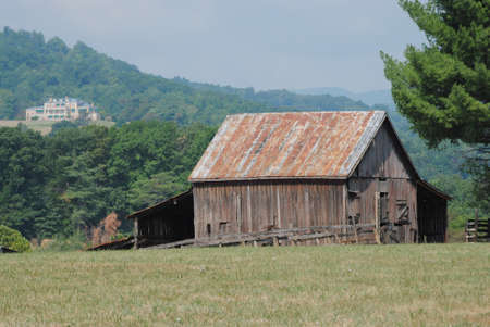 Rustic barn in field with mountains in the background.