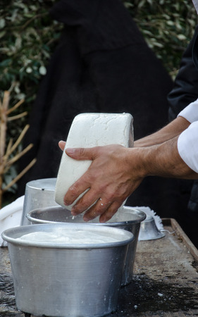 caciocavallo: hands of the elderly manufacturer of cheese while doing the cheese