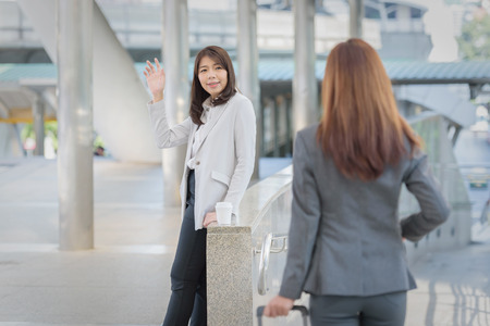 business woman greeting friends hand holding luggage Stock Photo