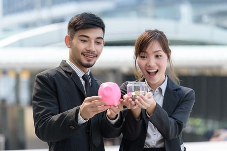 businessman hand holding pig pink  and businesswoman hand holding coin talking about savings money concept