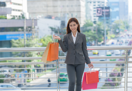 business woman or girl with shopping bags colorful online when payday in city structure Stock Photo