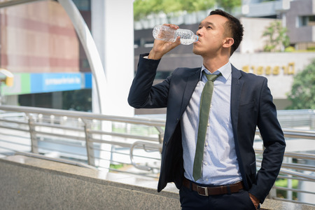 businessman standing drink water in area building when work hard concept time to work day