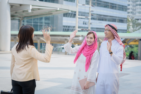 headcloth: businesswoman greetings arabian couple when first time to talking about business