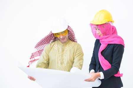 beautiful modern muslim architecture worker woman and arab young man work blueprint today on white background Stock Photo