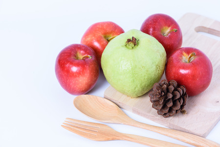 guayaba: pipe cone ,red apple,guava and fork and wooden spoon on white background
