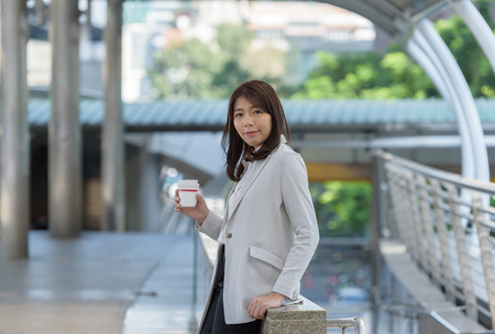 headcloth: business woman smile with hand holding a cup coffee Stock Photo