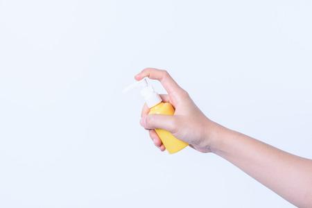 mano sosteniendo aerosol botella de plástico amarillo sobre fondo blanco