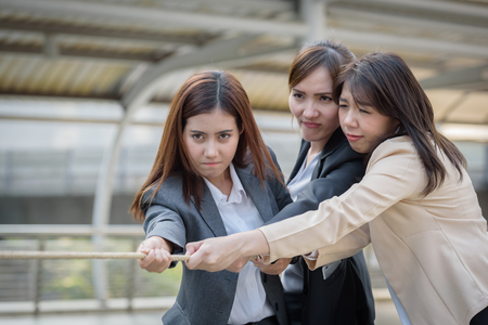businesswoman hand holding rope snatching, concept of business competitive