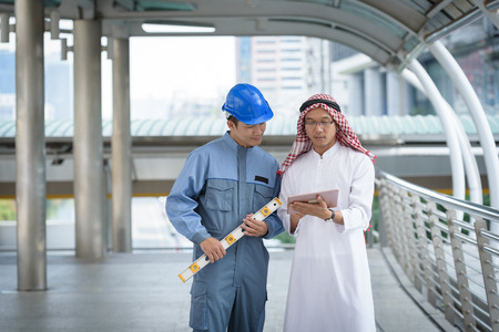 arab bussiness talking work  with engineer about plan project Stock Photo