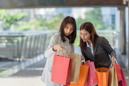 business woman and friend happy hand holding shopping bags online when payday in city structure