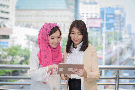 business woman and arab look report tablet on work day