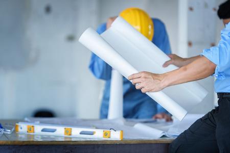 architectuur engineer bespreken project plan met en hand op blauwdruk