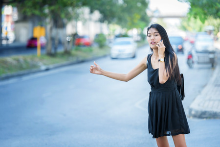 woman hand on mobile phone and wearing dress black walking on street Stock Photo