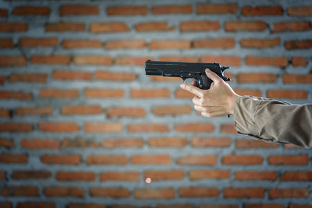 woman standing hand holding gun inside building structure Stock Photo