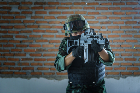 Soldier standing hand holding gun inside building structure