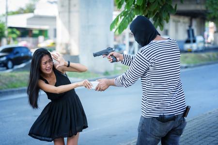 woman wearing dress black walking on street and criminal sack Stock Photo