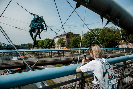 Stylish girl near the Vistula River in Krakow. Bridge across the river in Krakow. Young woman in town. Lady with a mobile phone. Travel to Poland. Europe