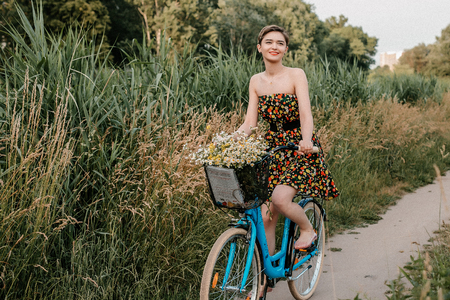 Young girl with a bike. Beautiful woman and flowers in the basket. Walking in the nature. travel