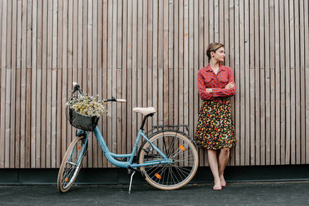 A wonderful girl travels by bike. Walking in the outdoors. Beautiful woman with a basket of flowers. Bike ride Imagens