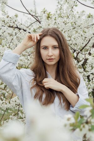 Girl walk in the flower garden. Young woman in a cherry orchard in spring. Photo of a girl between flowering trees. In Poland. Imagens