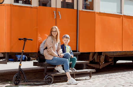 Young mother with her son near the orange tram. Scooter near the cafe in the old tram. Journey to Bydgoszcz. Poland/