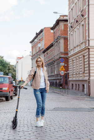 Young woman on a scooter in the city. Stylish girl rides a scooter. City trip. Poland Stock Photo