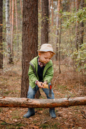 Little boy in a hat in the autumn forest. A boy with an ax near a fallen tree. Woodcutter hold ax.