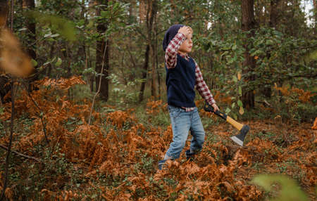 Little boy in the autumn forest. A boy with an ax near a tree. Woodcutter hold ax. Standing in the forest with axe.