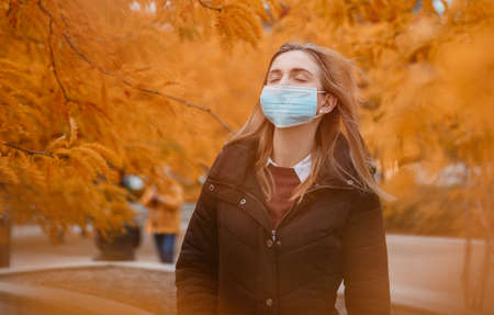 Girl in a mask near the business center. Woman in medical mask outdoors in autumn. Epidemic in the fall. Female student during the epidemic.