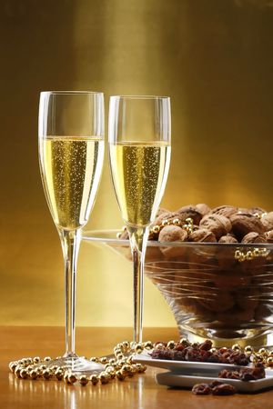 Glasses of champagne with gold background with walnuts, candels and dried raisins photo